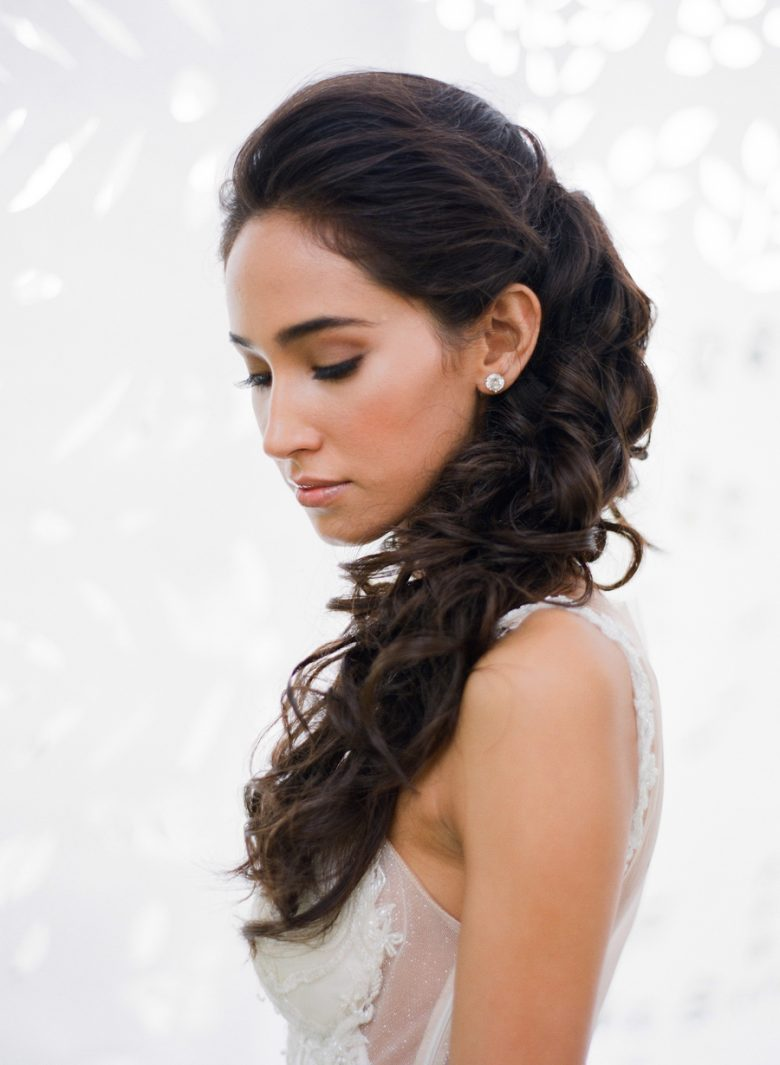 woman with long dark hair with loose curls cascading down shoulder for a wedding hairstyle
