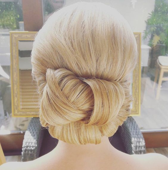 blond hair, sleeked back into a woven chignon for a wedding hairstyle