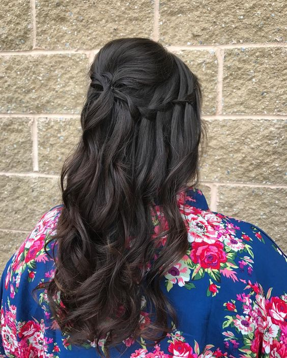 woman with long dark brown ombre hair in a waterfall braid from front to back, with loose curls for a wedding hairstyle