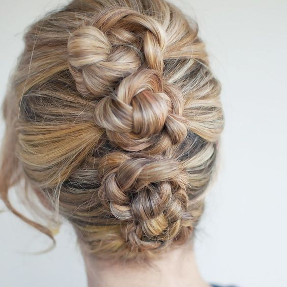 woman with honey, blond, and brown hair pulled back into four braided buns, vertically along back of head for a wedding hairstyle