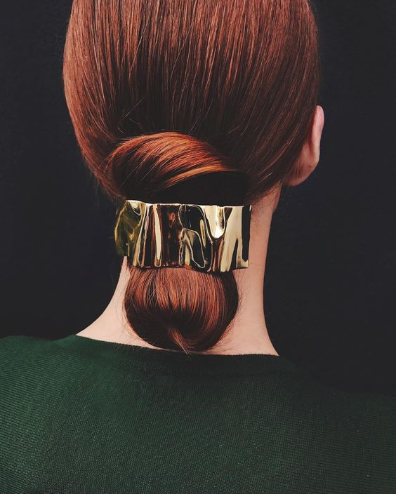 woman with sleek hair gathered into a low chignon with gold ripple accessory for a wedding hairstyle