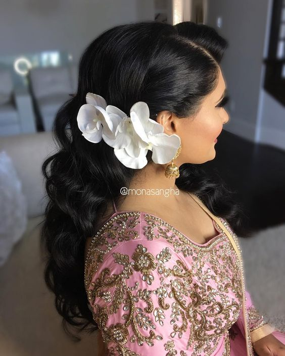 woman with very long dark curly hair, with the right side pulled back into a large double orchid fastener for a wedding hairstyle