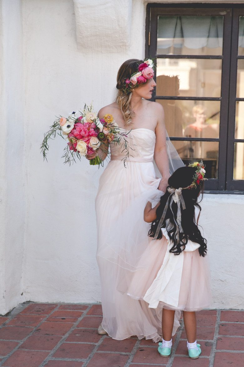 a bride holds her bouquet in one hand while looking to her left, as her flower girl clings to her