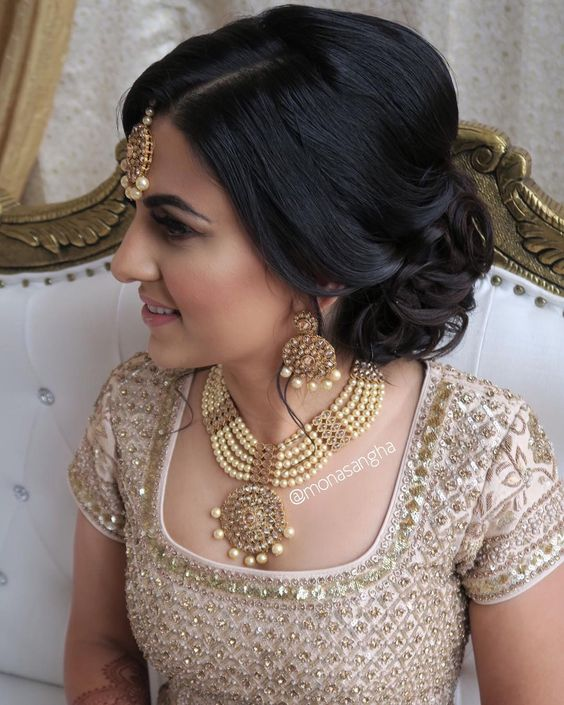 woman with dark hair gathered loosely into curls at the nape of her neck with gold and pearl tikka for a wedding hairstyle