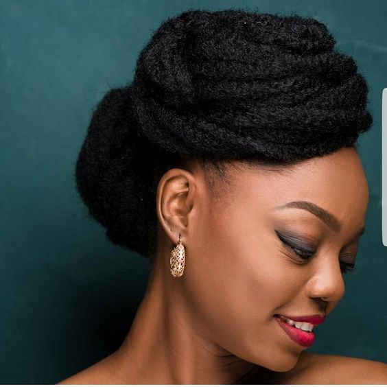 woman smiling with natural hair coiled on top and back of head for a wedding hairstyle