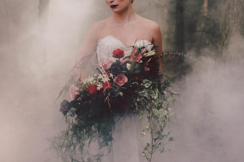 Bride holds a massive bouquet as she is enveloped in smoke
