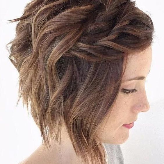 Woman with auburn hair in messy chin-length bob with two chunky, loose headband-style braids across the front, secured underneath hair for a wedding hairstyle