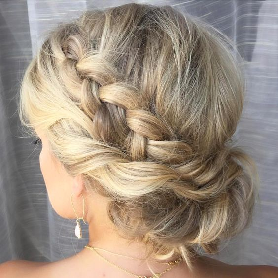 woman with a loose braid along left side of head with another layer of hair woven along underneath, gathered in the back for a wedding hairstyle