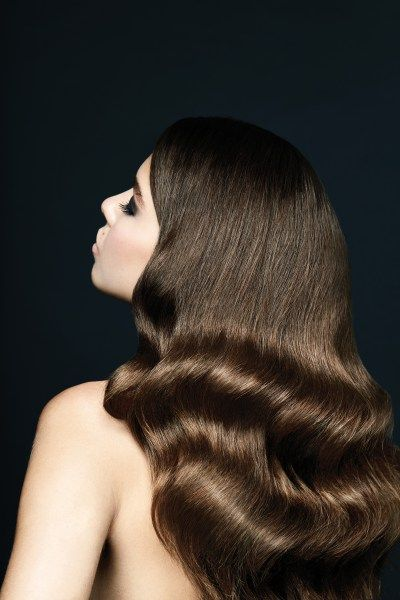 woman with very shiny, sleek, long dark hair with waves starting around shoulder height for a wedding hairstyle