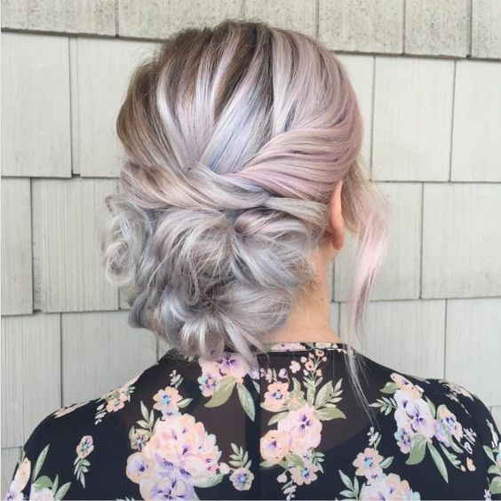 woman with pink and grey hair gathered into horizontal twist across the back of her head for a wedding hairstyle