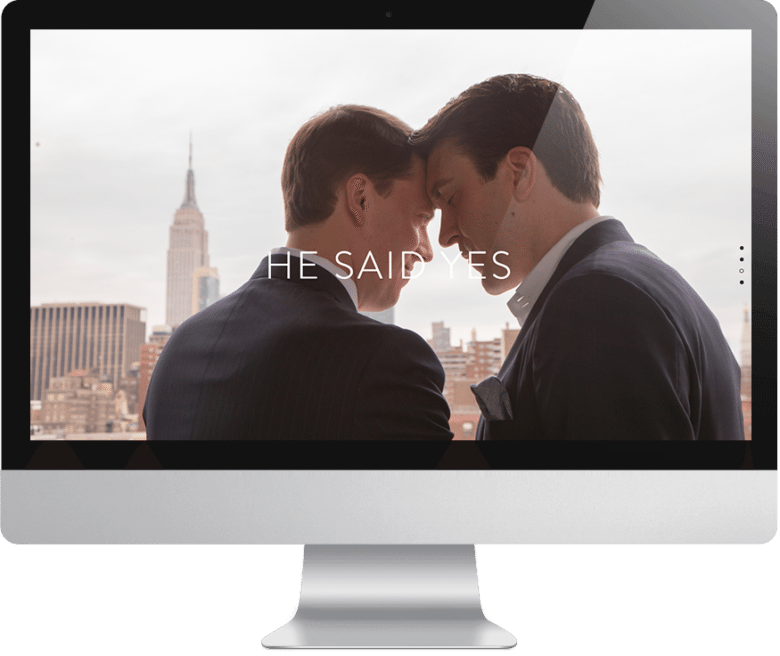 "Two happy men in suits with their foreheads together overlooking a city skyline with text overlay that reads ""he said yes"" on a computer monitor"