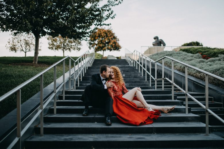woman with red hair wearing a red gown sitting on steps leaning against man in black tux sitting beside her