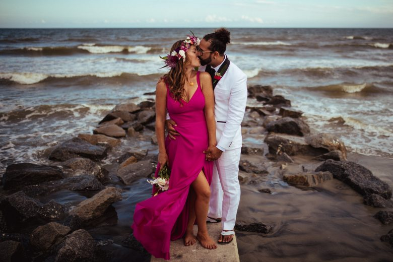 Woman with flower crown in bright pink dress and man in a white tux kissing on a rock on the beach in front of the ocean