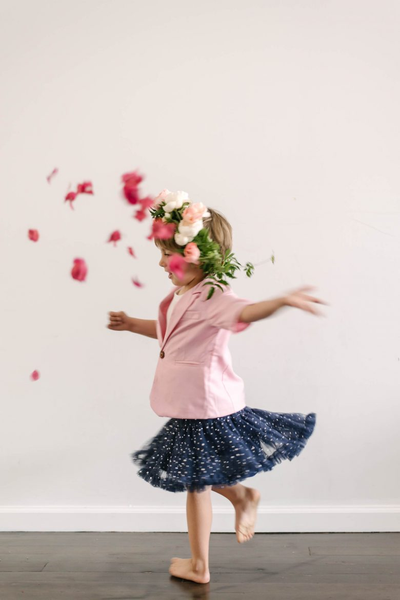 a young boy wearing a pink blazer and navy tutu throws flower petals