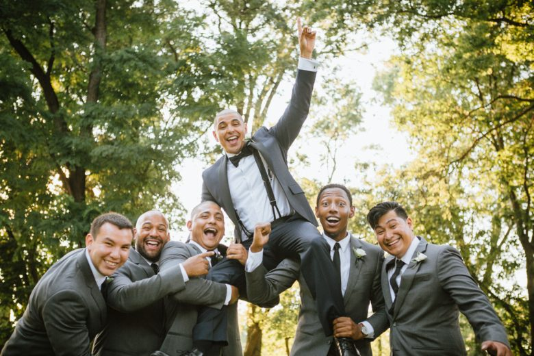 a group of jubilant men in suits hoisting groom up in a park