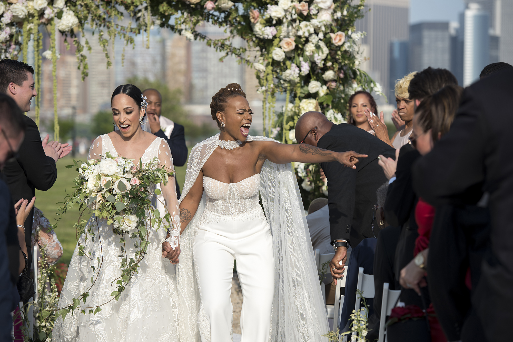 Two women walk back down the aisle after their wedding ceremony