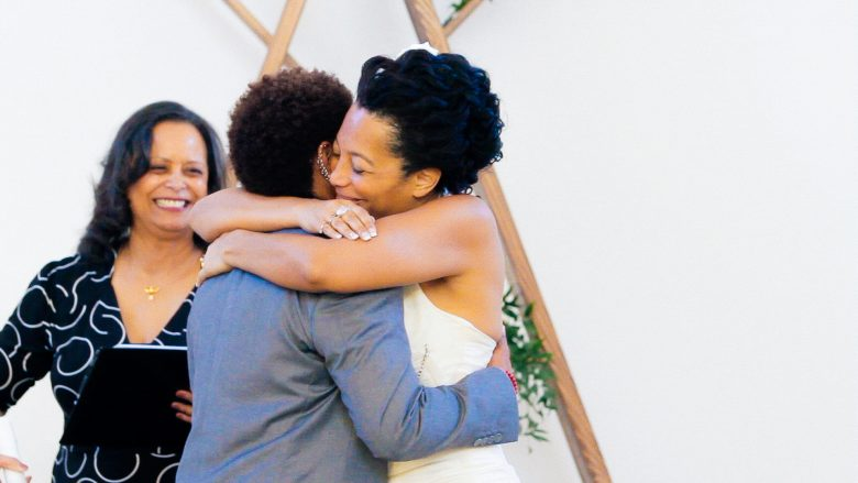 Black couple hugging at end of wedding ceremony