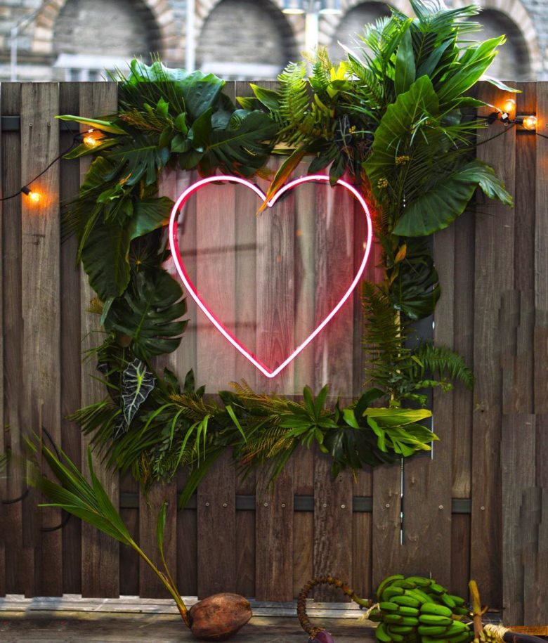neon-style pink heart inside tropical leaf frame