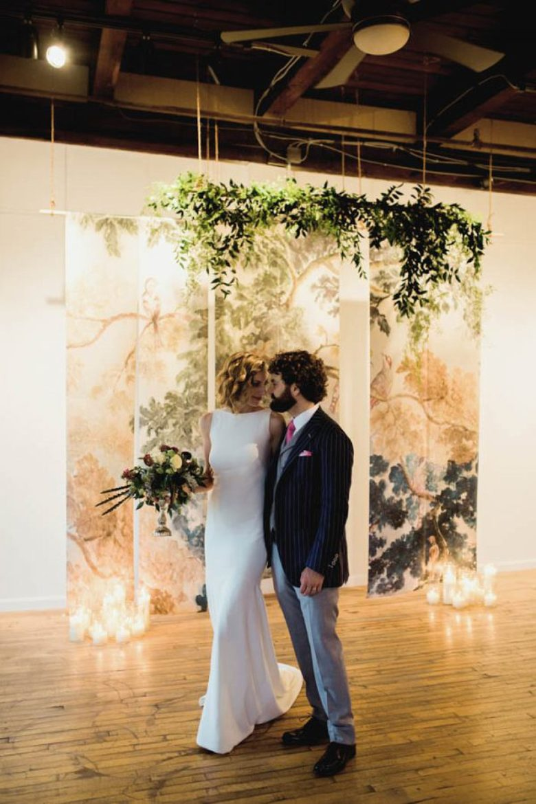 bride and groom in front of multi-piece fabric panel installation with greener and candles in gallery-style setting