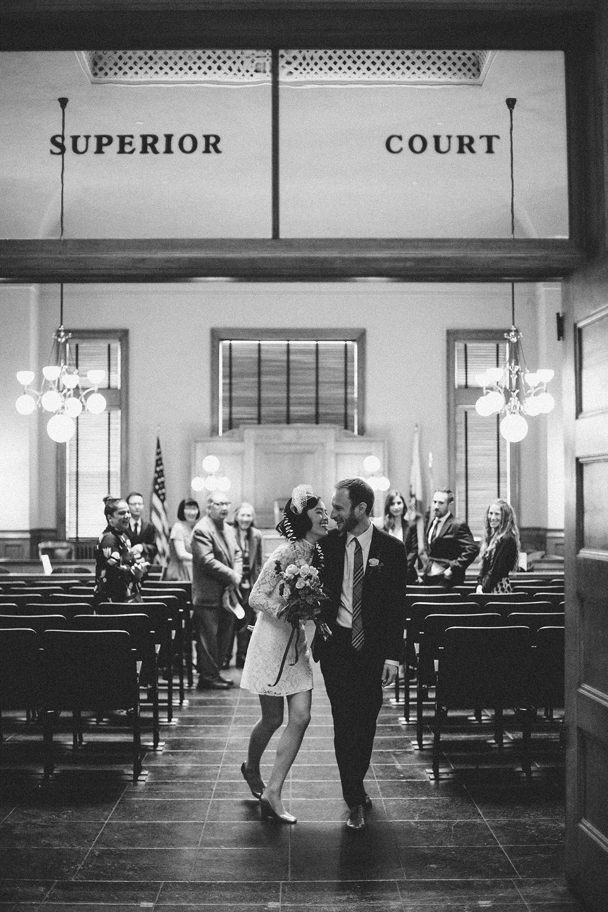 "black and white photo of a bride in a short dress and groom during recessional down the aisle of a room that says ""superior court"" above the door in a Gina Clyne photo"