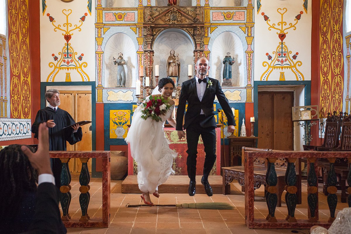 bride and groom jump over a broom at the altar of an ornately decorated chapel in a Gina Clyne photo