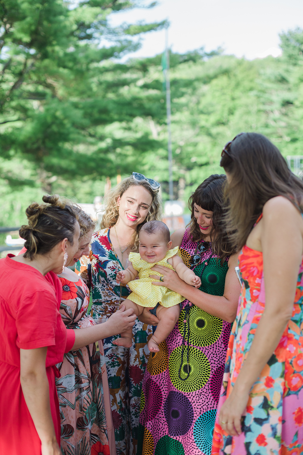 group of smiling women in brightly patterned dresses gather around one holding a baby in a Gina Clyne photo
