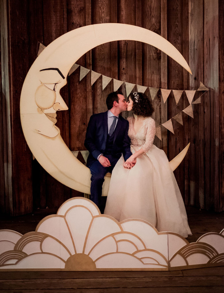 bride and groom sit kissing on hand-made paper moon in front of bunting with a deco-lights inspired 2-D cutout in front of them