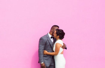 wedding couple standing in front of a pink wall