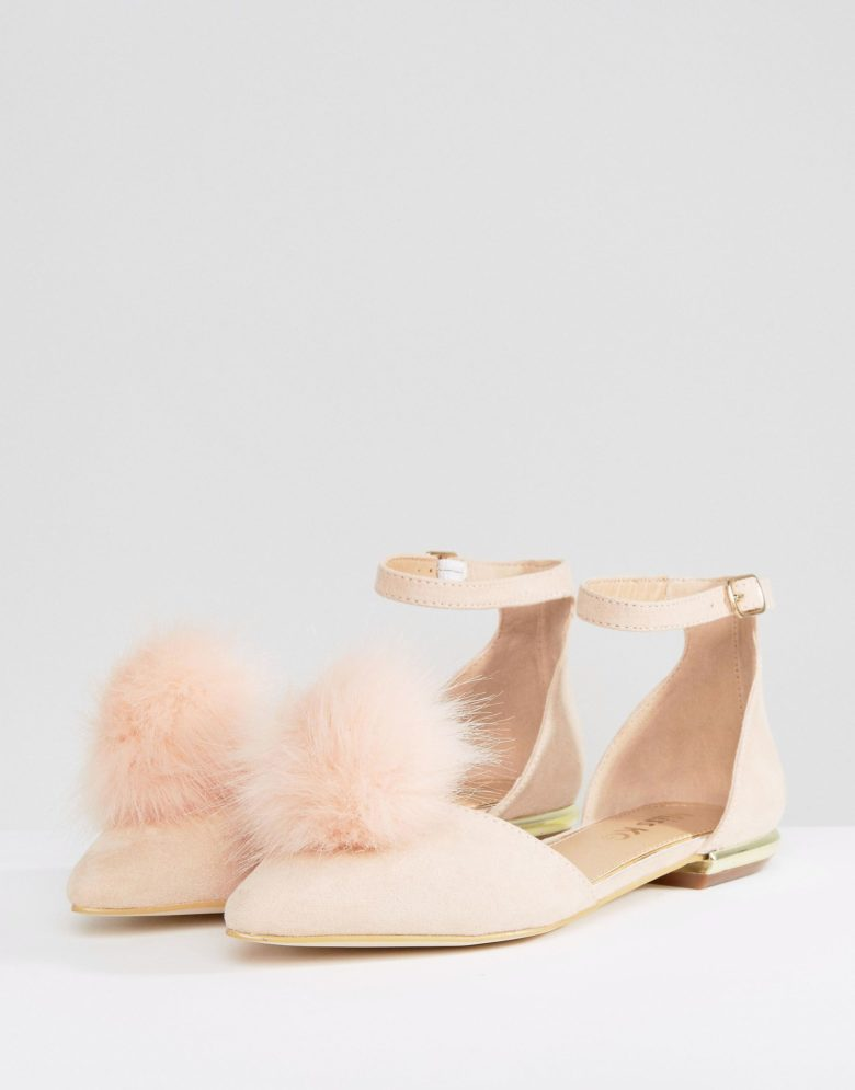 a pair of flats with a peach pom