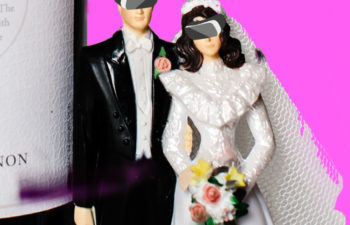 vintage bride and groom cake topper with digitally imposed VR headsets, in front of a pink background