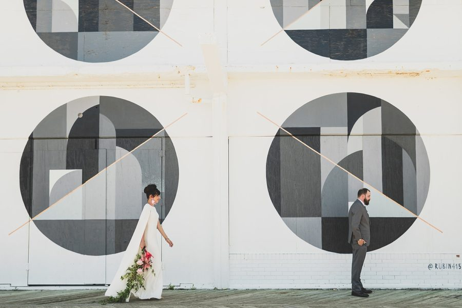 Bride and groom walking in front of a black and white mural