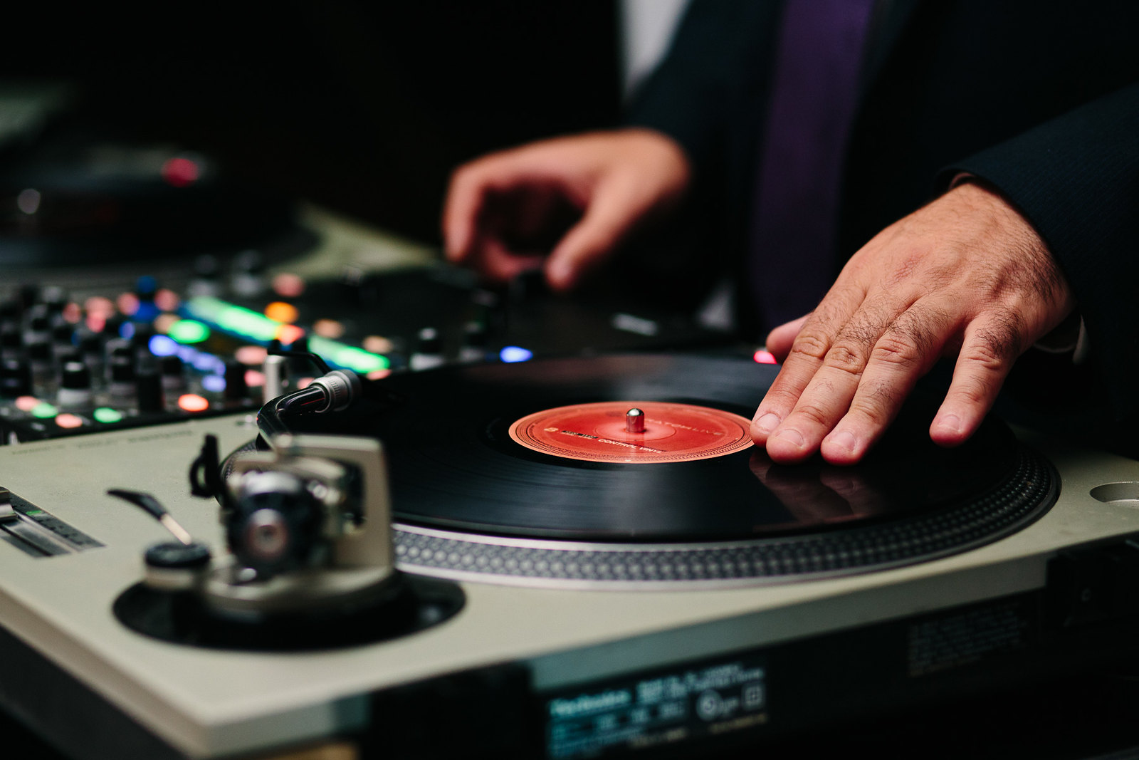 close up image of wedding DJ spinning records on a turntable