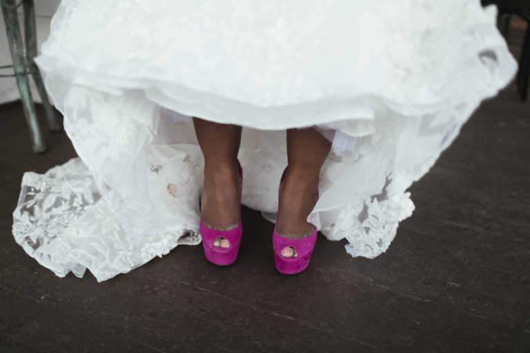 close up on a black bride lifting up her wedding dress slightly to show her hot pink platform wedding shoes