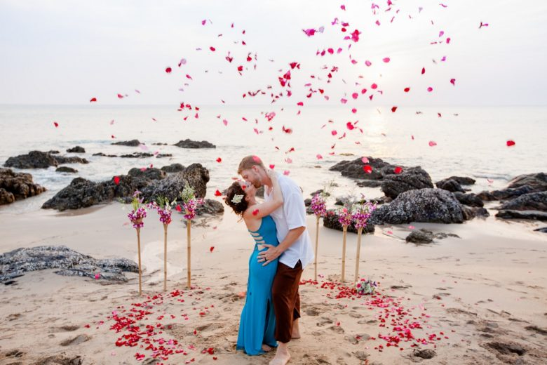 bride in a blue dress and groom kissing on a beach with red and pink flower confetti