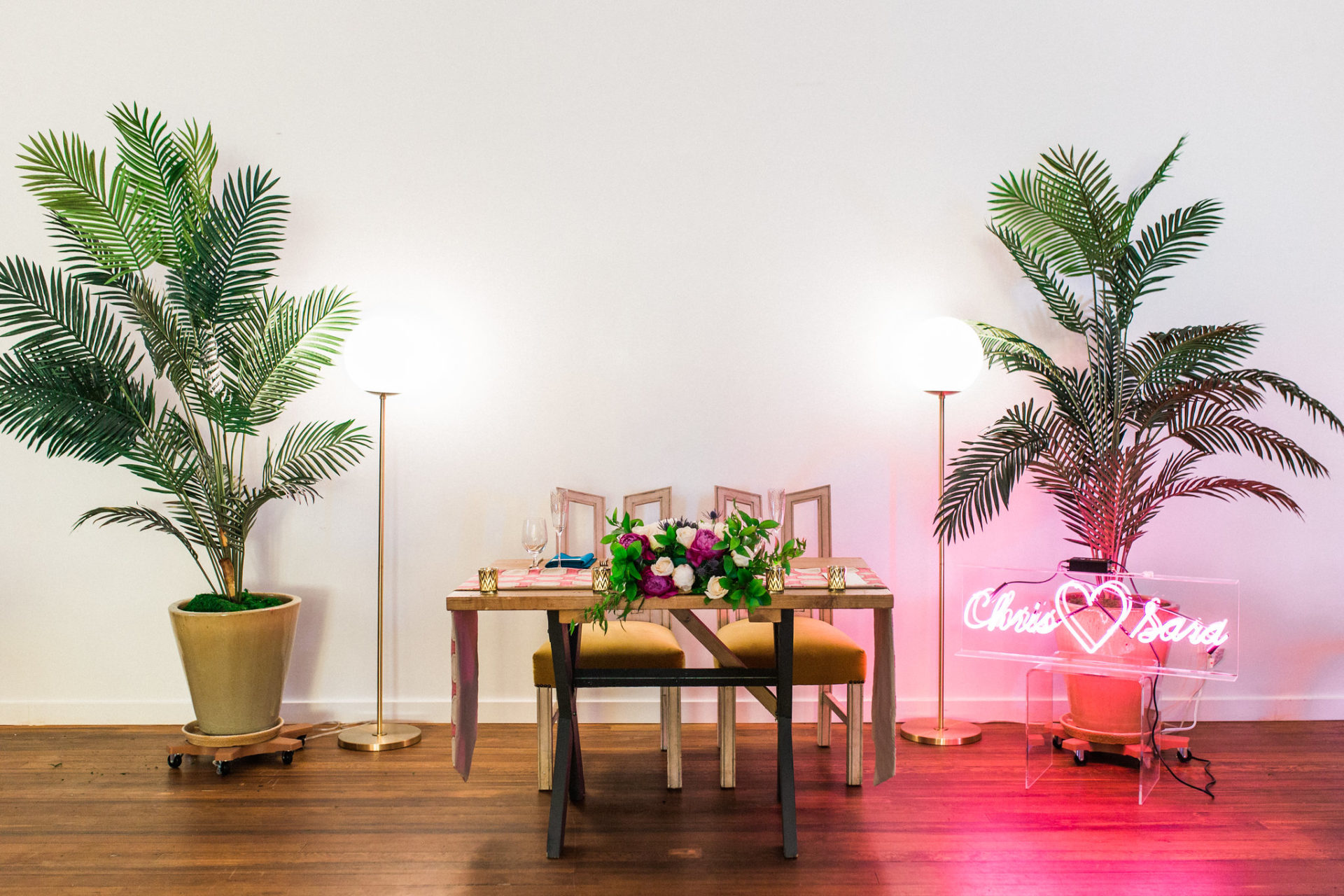 "a sweetheart table sits in a white room with wood floors. There are two potted tropical plants on either side of the table and a neon sign that says ""Chris <3 Sara"""