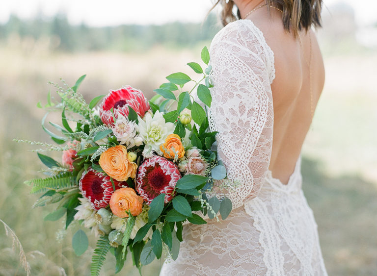 close up of a bride wearing a backless lace gown carrying a wild bridal bouquet with protea