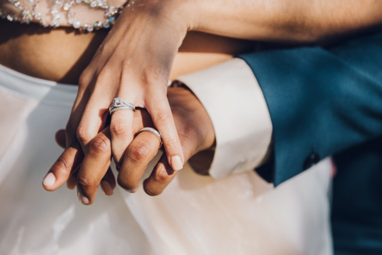 close up on the hands of a queer non-white couple wearing engagement rings and wedding bands
