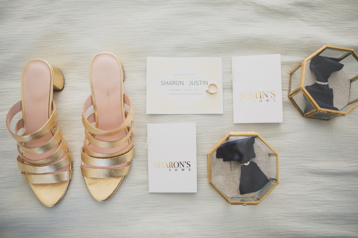 a layflat of day-of wedding essentials including gold high heeled shoes, printed foiled vows, and wedding rings