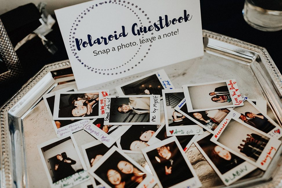 "a pile of instax mini photos sits on a silver tray next to a sign that says ""Polaroid Guestbook"""
