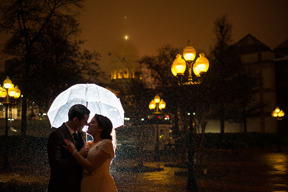 Bride and groom embrace under a clear umbrella on a rainy night surrounded by glowing streetlamps in a photo by You Are Raven