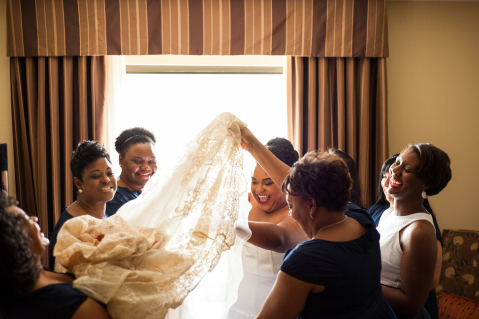 bride surrounded by bridesmaids helping her into dress in a photo by You Are Raven