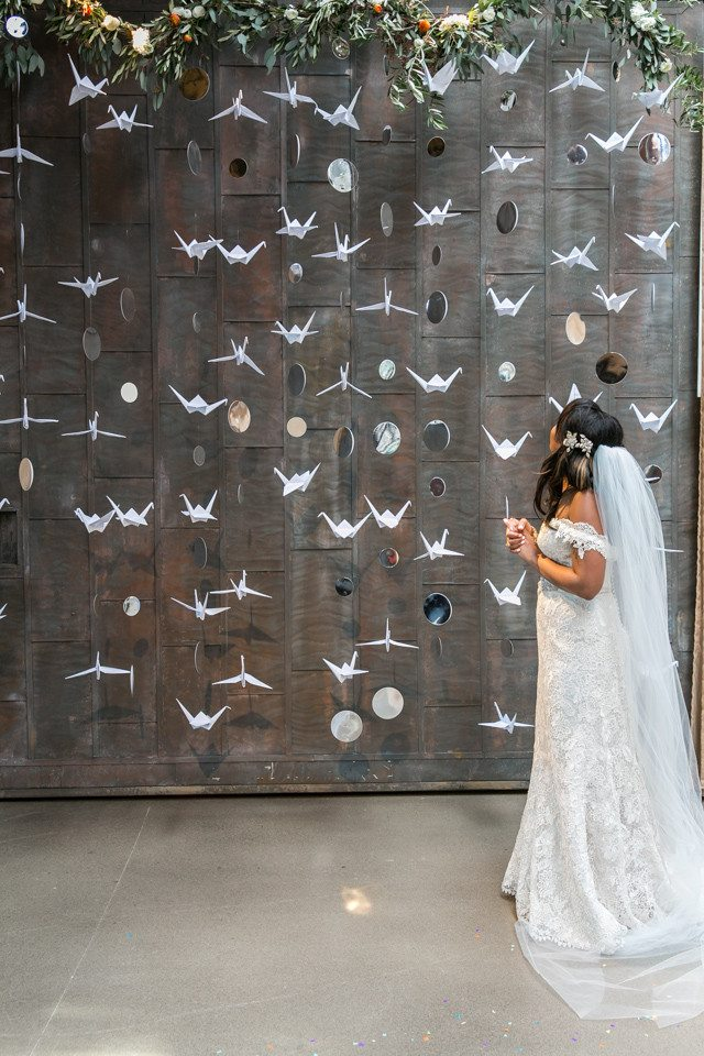 a bride stands in front of paper cranes and planet cutouts hanging vertically in front of a cement wall, bordered on top with a greenery garland