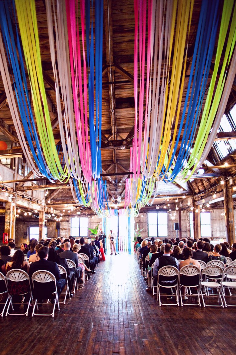 multi colored flagging tape installation at an indoor wedding ceremony
