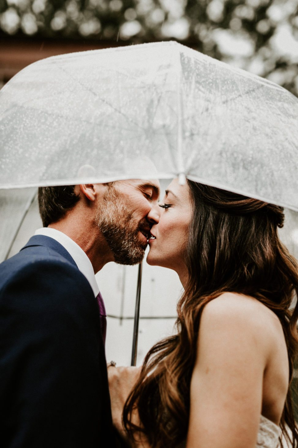 two people kissing under an umbrella