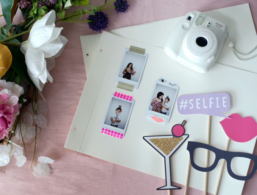 photo album pages with instant photos taped to them sitting beside a camera and photo props