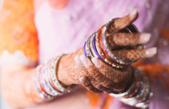 female hands with mehndi putting on sparkly bangle bracelets