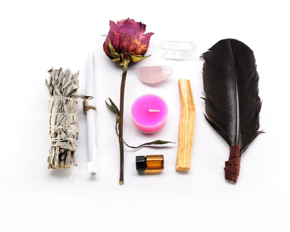 Rose, candle, feather, bottle, crystals, paper roll, wood piece, and bundle of dried leaves on white background