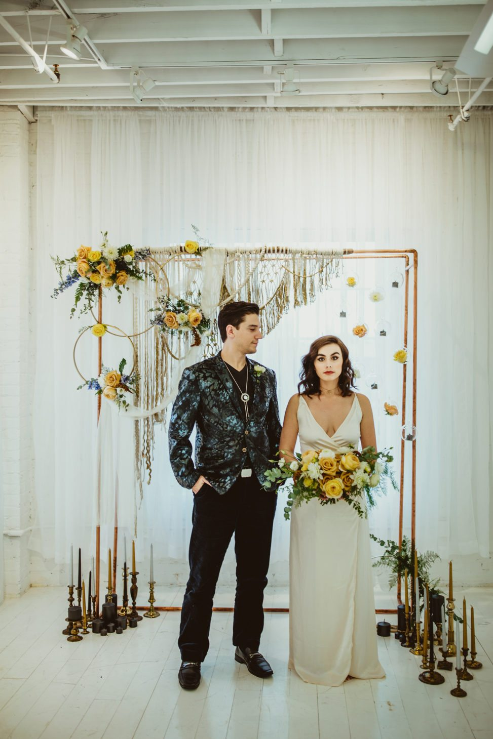 bride and groom standing near an alter with flowers, macrame, and candles
