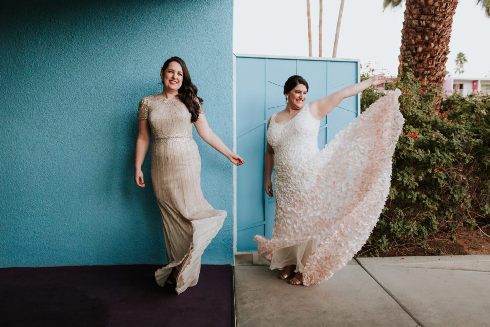 lesbian couple in wedding dresses standing in front of a blue wall at the Saguaro palm springs