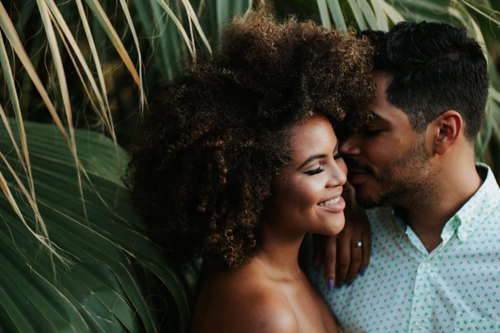 man leaning in to kiss woman with natural hair in front of palms